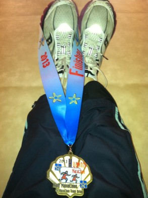 Resting in viparita karani and admiring my well earned finishers medal